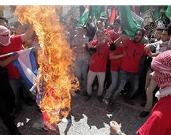 Palestinians burn the Israeli flag at a demonstration held in Ramallah in support of Palestinian terrorist prisoners held in Israeli jails.