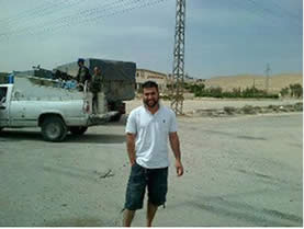One of the convoy's activists in Syria, photographed in front of one of the Syrian army vehicles which accompanied the convoy throughout its stay in Syria.