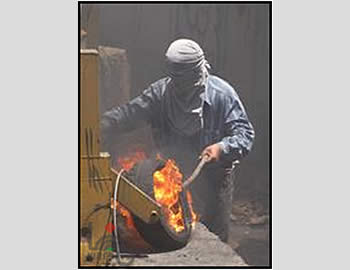 Palestinian sets fire to a tire at a riot in Bila'in (Wafa News Agency, July 13, 2012).