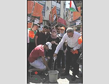 The  campaign organizers pour Israeli milk into a pail (Wafa News Agency, July 15, 2012).