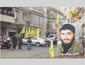 A picture of Hussein Ayoub alongside Hezbollah flags near his family's home in Salaa, Lebanon, after the drone was launched (Al-Manar TV, Lebanon, October 13, 2012).