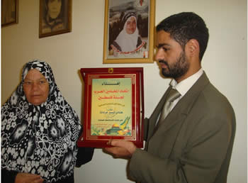 A member of the Arab Lawyers Union presents a framed plaque to the family of suicide bomber Hinadi Jaradat (Hamas forum, October 13, 2012).