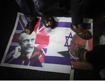 Demonstrators trample a picture of Lord Balfour and Mahmoud Abbas on the background of the British and Israeli flags (Hamas forum, November 3, 2012).
