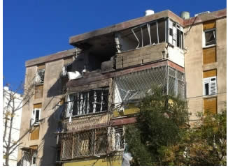 An apartment building in Kiryat Malachi takes a direct rocket hit, resulting in three dead and six wounded (Picture by Daniel Hagbi/Sderot Media Center, November 15, 2012).