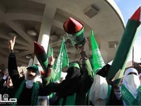 Demonstrators carry models of rockets at a rally in Nablus marking the 25th anniversary of the founding of Hamas
