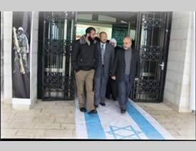 Hamas-faction members of the PLC walk on the Israeli flag on their way out of the Beir Zeit University exhibition marking the 25th anniversary of the founding of Hamas (Safa News Agency, December 5, 2012).