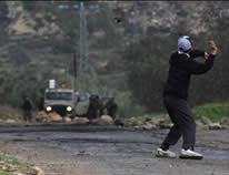 A Palestinian youth throws stones at an IDF force in the village of Qadoum (Wafa News Agency, December 21, 2012).