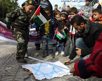 Kindergarten children in the Square of the Unknown Soldier in Gaza City participate in setting an Israeli flag on fire, with the assistance of an adult (Qudsnet website, November 25, 2012).