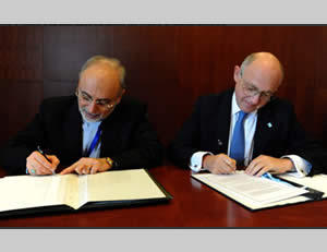 The foreign ministers of Iran (left) and Argentina (right) sign a memorandum of understanding to initiate a joint investigation