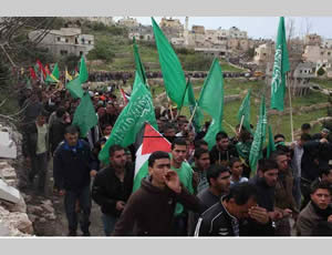 The funeral of Muhammed Samih Asfour in the village of Aboud, with mourners holding green Hamas flags (Paltoday website, March 8, 2013).