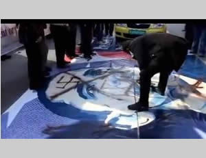 Palestinian demonstrators in Bethlehem walk on a picture of President Obama defaced with a swastika.
