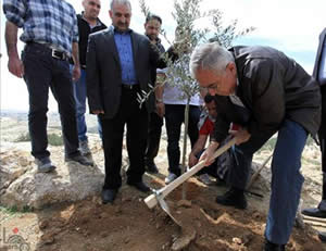 Palestinian Prime Minister Salam Fayyad plants an olive tree at Bab al-Shams to mark the 37th land day