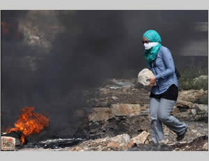 Palestinian youths throw stones at IDF forces during the weekly riot in the village of Qadoum, near Qalqiliya