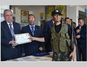 An Al-Futuwwa student at the Gamal Abdel Nasser School receives an award from senior members of the de-facto Hamas administration's ministry of education (Dunia Al-Watan, April 4, 2013)