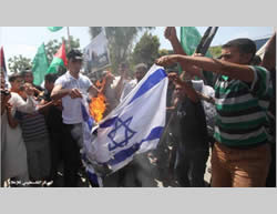 Burning the Israeli and American flags at the Global March to Jerusalem (GMJ) in the northern Gaza Strip