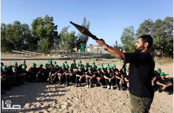 Children wearing green Hamas hats are shown how to fire an RPG at a Hamas summer camp (Filastin Al-'Aan, June 16, 2013).