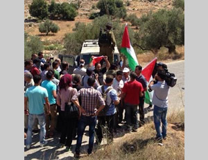 Abdallah Abu Rahma and Salah al-Khawaja block the entrance to the village of Deir Qadis as part of the popular resistance's protest