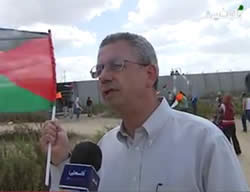 Mustafa Barghouti, le responsable de l'Initiative nationale palestinienne, accorde une interview à la fin de la conférence de Bil'in. En fond on aperçoit des Palestiniens lançant des pierres sur les forces de Tsahal (Chaîne Palestine, 4 octobre 2013)