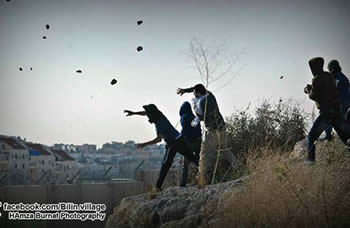 Rioting Palestinians throw stones at IDF forces in Bil'in during the weekly demonstration against the Israeli security fence
