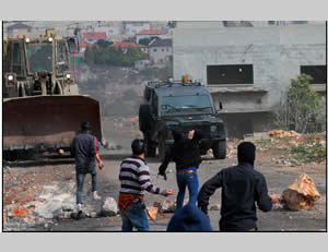 Palestinians throw stones at Israeli security forces in the village of Qadoum during the weekly Friday riot