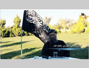 Sami al-Uraydi during the interview, which was published on October 21, 2013, standing beside the flag of the Al-Nusra Front (YouTube.com).
