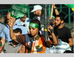 A child holds a plastic gun and a Hamas-affiliated flag.