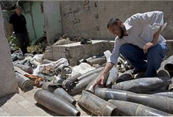 Hazem Abu Murad, commander of Hamas' demolitions unit, near unexploded shells which had been neutralized (Facebook page of Ghaza al-A'an, August 13, 2014).