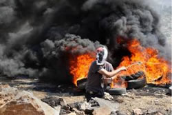 A masked man throws stones at Israeli security forces at a demonstration in Nablus.