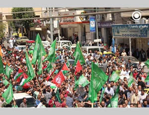 The funeral held in Hebron for the two terrorists. Participants hold green Hamas-affiliated and red and white Popular Front for the Liberation of Palestine (PFLP) flags