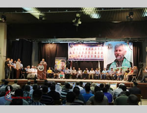 Mahmoud al-Zahar on stage during the ceremony for Hamas police killed in Operation Protective Edge. The rear of the stage is hung with the pictures of at least 70 operatives who were killed (Sarraj, September 30, 2014).