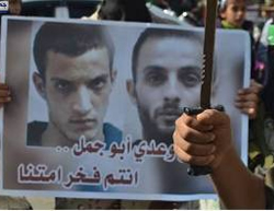 A sign with the pictures of the two terrorists. The Arabic reads,
