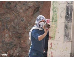 Masked Palestinian shoots fireworks at IDF forces during a riot in Hebron (PALDF, November 21, 2014).
