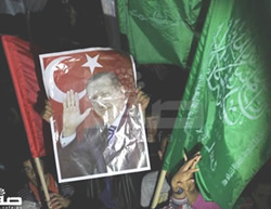 Palestinians hold Hamas flags, Turkish flags and a picture of Turkish President Erdogan at a march in the Gaza Strip held to celebrate his victory in the Turkish elections (Safa.ps, March 31, 2014).