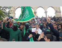 Hamas activists, some of them masked, wave a Hamas-affiliated flag at a demonstration on the Temple Mount (PALDF, December 19, 2014).