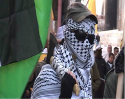 A masked terrorist operative holds an axe at a Fatah rally (PNN.ps, January 2, 2015).