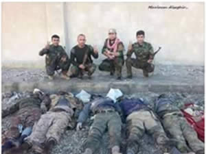 Kurdish fighters photographed next to bodies of ISIS operatives killed in the fighting.