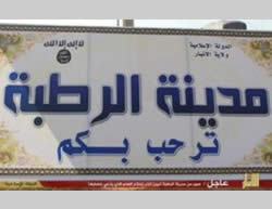 "The sign at the entrance to Rutba showing the ISIS insignia (on the left) and the words ""the Islamic State"""