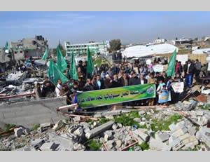 Demonstrators at Jahar al-Deek hold Hamas-affiliated flags. The Arabic reads,