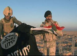 Iraqi soldiers folding up the ISIS flag and preparing to hoist the Iraqi flag