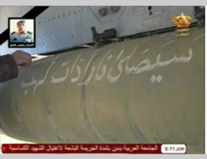 "Missile carried on a Jordanian plane, with the inscription: ""Great flames of fire will rain down."" Above the missile (on the left), there is a photo of Jordanian pilot al-Kasasbeh (Jordanian State TV, February 6, 2015)."