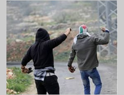 Young Palestinians throw stones at IDF forces in Bil'in during the weekly riot against the security fence and the settlements (Facebook page of Bil'in, February 13, 2015).