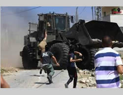 Palestinians throw stones at the Israeli security forces during the weekly riot in Kafr Qaddum (Facebook page of Kafr Qaddum, June 26, 2015)