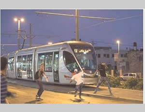 Palestinians throw stones and rocks at the light railway in Shuafat, east Jerusalem (Facebook page of QudsN, July 4, 2015).