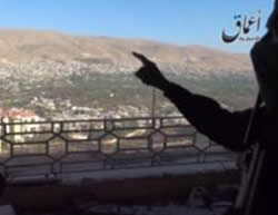 Armed ISIS operative pointing at the city and the mountain range overlooking it.
