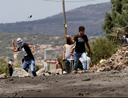 Palestinians throw stones at Israeli security forces in Kafr Qaddum during the weekly riot held to protest the Jewish communities (Wafa News Agency, August 28, 2015).