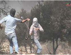 Palestinians throw stones at Israeli security forces during the weekly riot in Kafr Qaddum protesting the settlements (Facebook page of Kafr Qaddum, September 3, 2015)