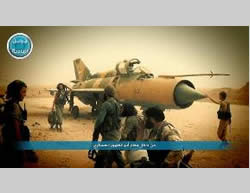Al-Nusra Front operatives next to a Syrian fighter plane at the Abu al-Duhur military airbase (Twitter account affiliated with the Al-Nusra Front, September 10, 2015)