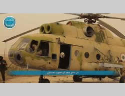 Al-Nusra Front operatives next to a Syrian helicopter at the Abu al-Duhur military airbase.