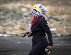 A masked Palestinian woman wearing a yellow Fatah headband collects stones to throw at IDF forces during riots in Al-Bireh.
