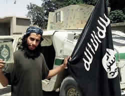 Abdelhamid Abaaoud with the ISIS flag. The picture was taken in Syria (Dabiq, Issue 7, February 2015)